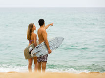 Young surfers couple on the beach Stock Photos