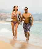 Young surfers couple on the beach Royalty Free Stock Image