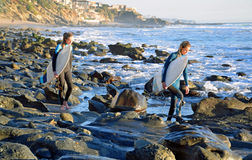 Young surfers head for the surf at Mountain Street Beach in Laguna Beach, California. Stock Image