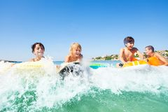 Young surfers riding the waves on body boards stock images