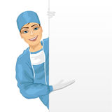 Young surgeon in blue scrun suit presenting empty presentation banner Royalty Free Stock Photo