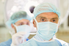 Young surgeon tying older surgeons mask Royalty Free Stock Photo