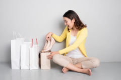 Young surprised asian woman sitting besides row of shopping bags Royalty Free Stock Image