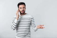 Young surprised bearded man talking on cellphone. Stock Image