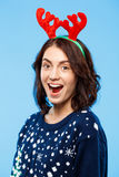 Young surprised beautiful brunette girl in knited sweater and christmas reindeer antlers smiling  over blue background. Stock Photography