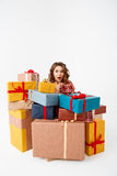 Young surprised beautiful curly girl among gift boxes Isolated Stock Photos