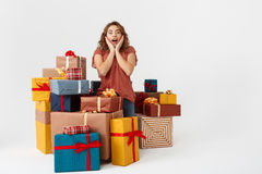 Young surprised beautiful curly girl among gift boxes Isolated Stock Image