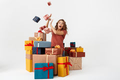 Young surprised beautiful curly girl among lying and falling gift boxes Isolated Stock Photo