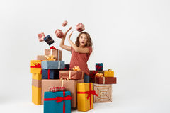 Young surprised beautiful curly girl among lying and falling gift boxes Isolated Royalty Free Stock Photography