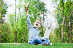 Young surprised boy with a books and laptop Royalty Free Stock Photos