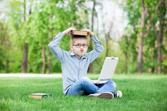 Young surprised boy with a books and laptop Stock Photos