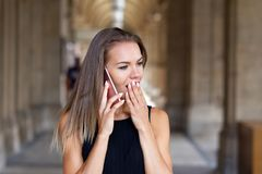 Young surprised brunette woman calling by phone royalty free stock photo