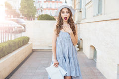 Young surprised brunette woman looking at camera outdoors Stock Image