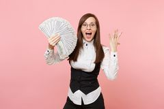 Young surprised business woman in glasses holding bundle lots of dollars, cash money spreading hands isolated on pink. Background. Lady boss. Achievement career royalty free stock photos