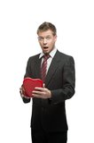 Young surprised businessman holding red heart Stock Image