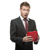 Young surprised businessman holding red heart Stock Photo