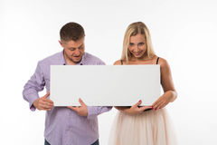 Young surprised couple showing presentation pointing placard. Royalty Free Stock Images