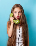 Young surprised girl with green handset Royalty Free Stock Image