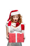 Young surprised girl holding christmas gift. Young red-haired european surprised girl in santa hat and red and white scarf holding christmas gift stock photo