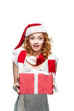 Young surprised girl holding christmas gift. Young red-haired european surprised girl in santa hat and red and white scarf holding christmas gift royalty free stock images