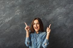 Young surprised girl pointing up. Young surprised girl pointing two fingers up. Young cheerful smiling woman showing upward at gray studio background with copy Royalty Free Stock Photo