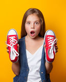 Young surprised girl with red gumshoes. On yellow background Royalty Free Stock Photos