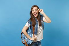Young surprised happy woman student with opened mouth in white t-shirt and denim clothes with backpack holding glasses royalty free stock images
