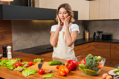 Young surprised housewife woman cooking in a kitchen Stock Photo