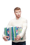 Young surprised man holding big heavy gift. Young casual surprised caucasian man holding big heavy christmas gift with amazed expression royalty free stock photos
