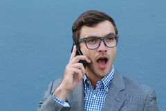 Young surprised man talking on his mobile phone  on blue background Stock Photo