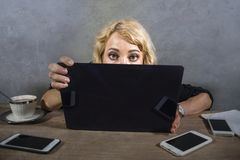 Young surprised and stressed business woman at office desk looking intense to computer screen surrounded by mobile phones in overw stock photos