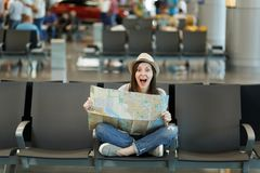 Young surprised traveler tourist woman with crossed legs hold paper map, search route waiting in lobby hall at. International airport. Passenger traveling royalty free stock photo
