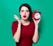Young surprised woman with alarm clock Stock Image