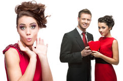 Young surprised woman and couple holding red heart on white back Royalty Free Stock Photography