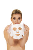 Young surprised woman with facial mask Stock Photography