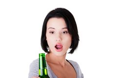 Young surprised woman holding a bottle of beer Royalty Free Stock Images