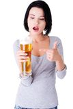Young surprised woman holding a glass of beer Stock Photography