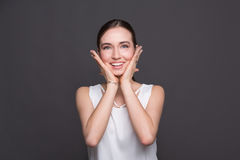 Young surprised woman holding her head portrait. Beautiful girl heard good news, posing at camera, dark background Royalty Free Stock Image