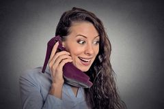 Young surprised woman holding high heeled shoe in hand as phone Royalty Free Stock Photo
