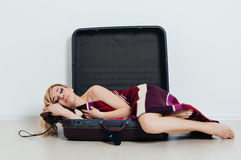 Young surprised woman lies in a suitcase royalty free stock photo