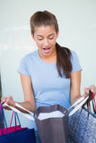 Young surprised woman looking at her shopping bags Stock Photo