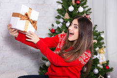 Young surprised woman opening gift box near decorated christmas Stock Photo