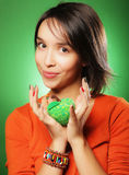 Young surprised woman over green background Stock Photo