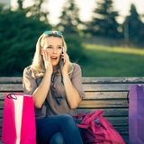 Young surprised woman sitting on a bench after shopping Royalty Free Stock Images