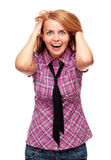Young surprised woman standing on white background. Young surprised and redheaded woman wearing checked shirt and standing on white background Royalty Free Stock Photo