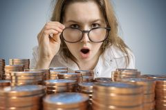 Young surprised woman wins money. A lot of coins in front royalty free stock image