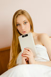 Young surprized blonde female with her tablet pc Stock Photo