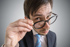 Young suspicious businessman is looking at you through glasses Stock Photos