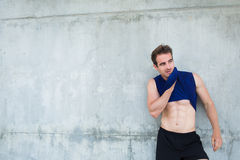Young sweating male jogger taking break after training. Tired fit man with muscular body resting after morning run while standing against street wall background Royalty Free Stock Image