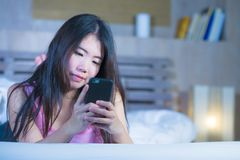 Young sweet and beautiful Asian Chinese 20s or 30s woman smiling happy lying on bed using internet mobile phone dating or sending. Text at night in social media stock photography